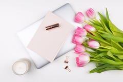 La configuration féminine d'appartement, espace de travail de vue supérieure avec des tulipes fleurit le bouque Images stock