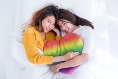 La configuration lesbienne de couples de l'Asie LGBT sur l'arc-en-ciel de lit et d'étreinte colorent l'oreiller Photos stock