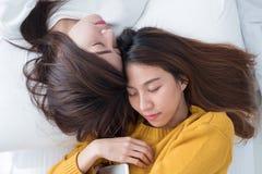 La configuration lesbienne de couples de l'Asie LGBT sur le lit et ferment l'oeil avec bonheur Photographie stock libre de droits
