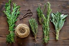 La configuration plate avec les herbes et la verdure fraîches pour sécher et faire des épices a placé sur le fond en bois de cuis photo stock