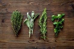 La configuration plate avec les herbes et la verdure fraîches pour sécher et faire des épices a placé sur le fond en bois de cuis images libres de droits