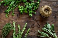 La configuration plate avec les herbes et la verdure fraîches pour sécher et faire des épices a placé sur le fond en bois de cuis photos libres de droits