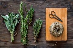 La configuration plate avec les herbes et la verdure fraîches pour sécher et faire des épices a placé sur le fond en bois de cuis image libre de droits