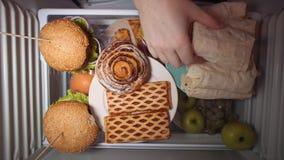 La configuration plate de la main prennent la nourriture la nuit avec sur les étagères du réfrigérateur banque de vidéos