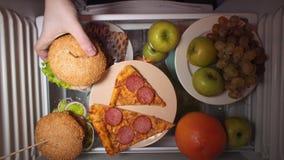 La configuration plate de la main prennent la nourriture la nuit avec sur les étagères du réfrigérateur clips vidéos