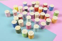 La configuration plate du fil coloré roule pour coudre sur le backgrou de deux tons Photo stock
