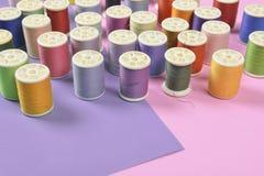 La configuration plate du fil coloré roule pour coudre sur le backgrou de deux tons Photographie stock libre de droits