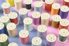 La configuration plate du fil coloré roule pour coudre sur le backgrou de deux tons Image stock