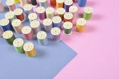 La configuration plate du fil coloré roule pour coudre sur le backgrou de deux tons Images stock
