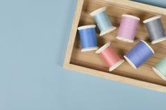 La configuration plate du fil coloré roule pour coudre sur le fond bleu, Images stock