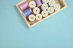 La configuration plate du fil coloré roule pour coudre sur le fond bleu, Images libres de droits
