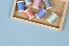La configuration plate du fil coloré roule pour coudre sur le fond bleu, Image libre de droits