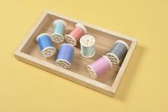 La configuration plate du fil coloré roule pour coudre sur le fond jaune Photos stock