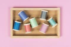 La configuration plate du fil coloré roule pour coudre sur le fond rose, Images stock