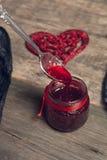 La confiture de framboise a versé d'une cuillère dans le pot près du coeur rouge sur le fond en bois Amour Jour de Valentine Vue  Photo libre de droits