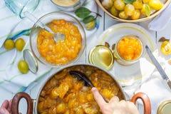 La confiture de prune dans le pot et la femme le met dans des pots Image stock