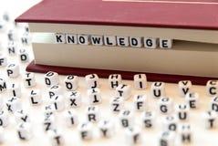La conoscenza di parola scritta con le lettere fra un libro impagina il fondo bianco con le lettere sparse intorno al concetto de fotografie stock libere da diritti