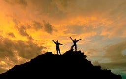 La conquista della sommità, le siluette di due genti sopra il mountai fotografia stock libera da diritti