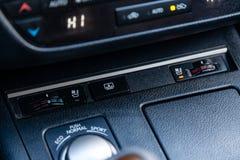 La consola de control central en el panel dentro del control del clima de los botones del primer del coche y de los asientos cale imagenes de archivo