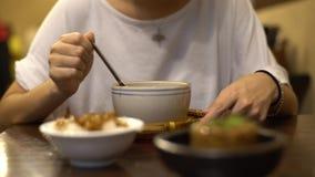 la consommation asiatique de la femme 4K chiken la soupe et le bol de riz pour le dîner dans le restaurant banque de vidéos