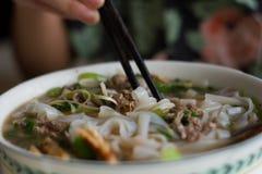 la consommation d'un bol de soupe de nouilles vietnamienne de boeuf Pho BO avec la côtelette colle Image stock
