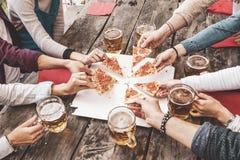 La consommation heureuse d'amis emportent la pizza et la bi?re potable photos stock