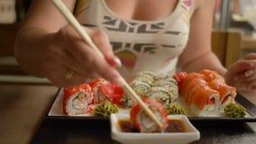 La consommation japonaise, mains de fille avec des bâtons plonge des sushi dans la sauce de soja dans le restaurant clips vidéos