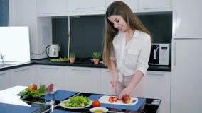 La consommation saine, fille coupe le poivron rouge pour la salade sur la planche à découper sur la table de cuisine banque de vidéos