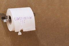 La constipation de mot écrite sur un papier de tolet Photo stock