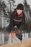 La construcción de la cabaña de madera, un trabajador joven aserró la madera, usando a Fotos de archivo