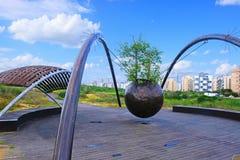 La construcción de las estructuras del metal con una esfera del metal suspendida de ellas con un sycomorus de los ficus del árbol imagenes de archivo