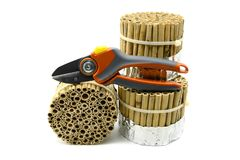 La construcción de un hotel del insecto con los palillos de lámina y de bambú en blanco es foto de archivo