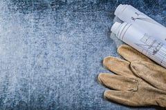 La construcción rodada planea los guantes de cuero de la seguridad en la parte posterior metálica Imágenes de archivo libres de regalías