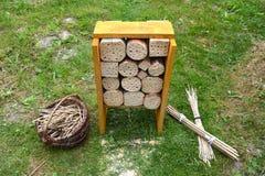 La construcción y las cañas del hotel del insecto en cesta en primavera cultivan un huerto Imagen de archivo