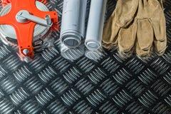 La construction prévoit des gants de sécurité mesurant la bande sur le métal cannelé photos libres de droits