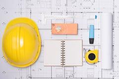 La construction pr?voit avec le casque et les outils de dessin sur des mod?les photographie stock