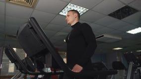 La construction sportive masculine, établit dans le gymnase Un homme s'exerce sur un tapis roulant au club sportif clips vidéos