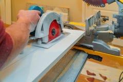 La construction transformant le panneau en bois d'équilibre de coupe à la maison dessus avec la circulaire de main a vu images libres de droits