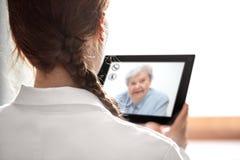La consultazione di Doctorcon telemedicina o telehealth, anziano fotografia stock libera da diritti