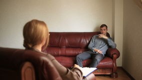 La consultazione di uno psicologo, un terapista femminile sta consultando un paziente con un uomo con un disturbo di ansia stock footage