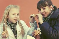 La consumición adolescente feliz de las muchachas las hamburguesas y francés libera Fotos de archivo libres de regalías