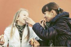 La consumición adolescente feliz de las muchachas las hamburguesas y francés libera Imágenes de archivo libres de regalías