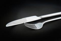 La consumición de los utensilios/bifurca y cuchillo en fondo negro Imagen de archivo libre de regalías