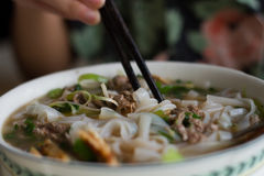 la consumición de un cuenco de la sopa de fideos vietnamita Pho BO de la carne de vaca con tajada se pega imagen de archivo