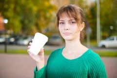 La consumición joven feliz de la muchacha del estudiante se lleva el café Imagen de archivo
