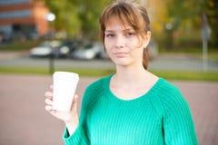 La consumición joven feliz de la muchacha del estudiante se lleva el café Foto de archivo