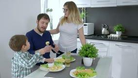 La consumición sana, pequeño muchacho alimenta a la madre durante el desayuno de la familia almacen de video