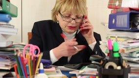 La contable mayor de la mujer se sienta en la tabla y comunica vía smartphone almacen de video