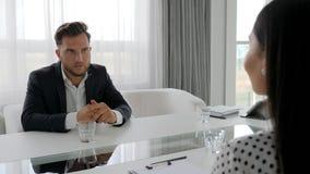 La conversación del individuo infeliz y del psicólogo que se sientan en la tabla, hombre en deprimido habla de problemas con la m metrajes