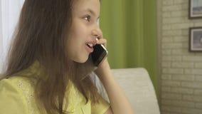 La conversación telefónica distrae a la muchacha del adolescente mientras que hace su preparación Foto de archivo libre de regalías